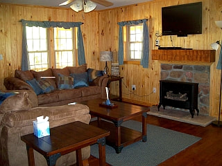 Living room with two couches, tv, and fireplace in Star Falls Resort Cabin